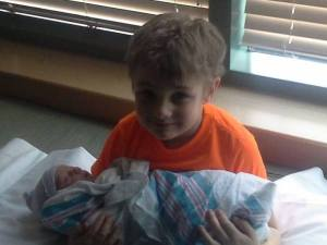 Conner holding his new baby sister